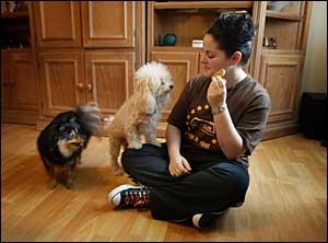 PLAYFUL MOMENT WITH HER DOGS: Dana Kwiatkowski, 17, feeds treats to her poodle, Milo, and Arwen, her Pomeranian, in her living room in Cooper City. Dana, who was hospitalized after her doctor began to reduce her dose of Paxil, is now using other medication to control her depression. JOE RIMKUS JR./HERALD STAFF